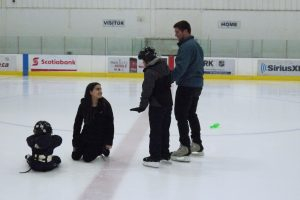 Two York University students helping young skaters on the ice
